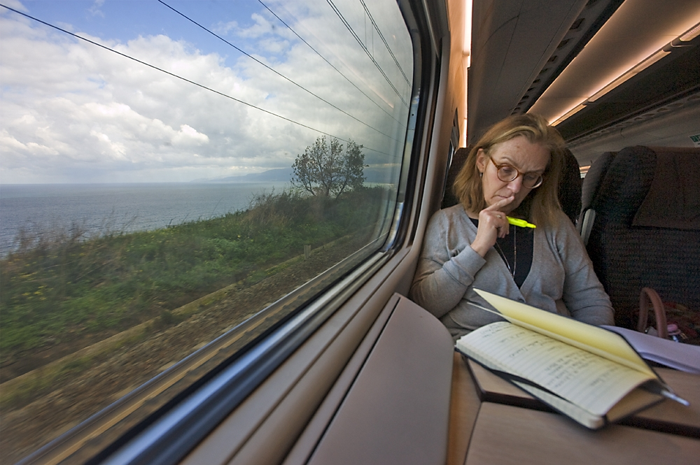 Caitlin reviews her research notes on a train to Naples.